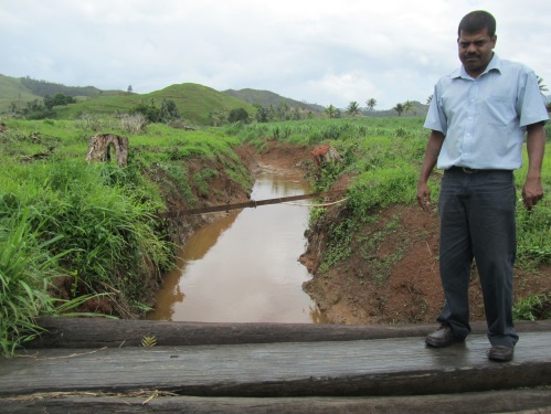 Executive Manager of LCPA Mukesh Kumar stands by a drain that was funded by Fairtrade Premiums; locals estimate that the drain saves over a thousand tonnes of cane from being flooded annually.